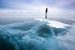 Girl photographer walking on cracked ice of a frozen lake Baikal