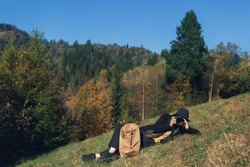 girl photographer with backpack lies on slope and shoot wildlife in mountains in autumn.