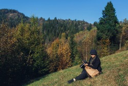 girl photographer with backpack sits on slope and shoot in mountains in autumn.