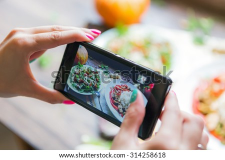 Girl photographs cooked meal using her smartphone