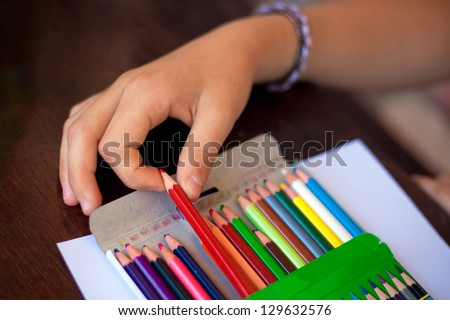 Girl picking a color crayon. Macro shot. - stock photo