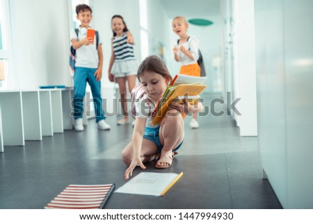 Girl picking books. Cute dark-haired girl picking up books from floor after boy pushed her #1447994930