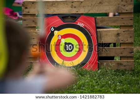 Girl playing archery game, aiming and shooting with rubber cup arrow #1421882783