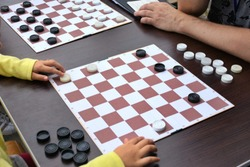 Girl playing checkers outdoor. Checkers game board on wooden table with black and white checkers
