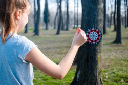 Girl playing darts outdoors in the park.Copy space