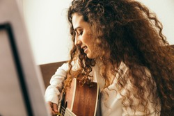Girl playing guitar and singing. Young woman with long hair studying music at home. She plays acoustic guitar and sing alone at home.