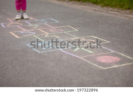 girl playing hop-scotch in playground  - stock photo