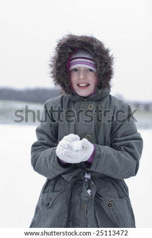girl playing in the snow making snow balls