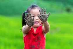 Girl playing outdoor showing dirty muddy hands. Happy childhood.