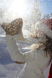 girl playing snow Christmas holiday white background shining snowflakes snowing gloves white Santa Klaus hat red sparkling sunny day winter festive season freedom happiness teenager throwing snow