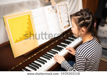 Girl playing the piano at home Stock photo ©