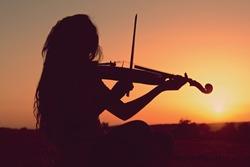Girl playing the violin at suns