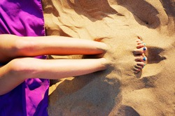 Girl playing to bury your feet in the sand on the beach
