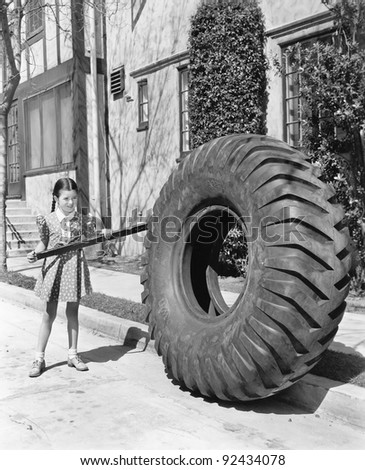 Girl playing with a huge tire and stick