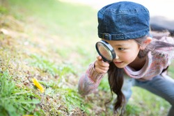 Girl playing with a magnifying glass
