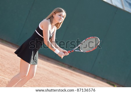 Girl playing with a tennis racquet on a tennis court for lessons.