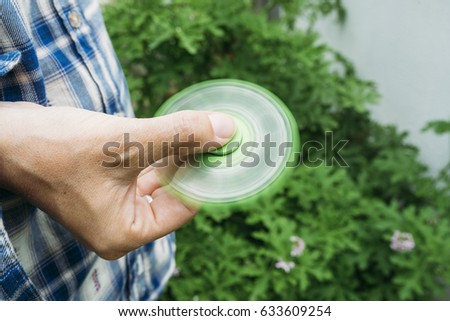 Girl playing with a Tri Fidget Hand Spinner outdoors