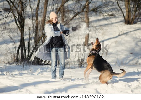 Girl playing with dog on the snow