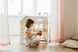 Girl playing with doll house in children room