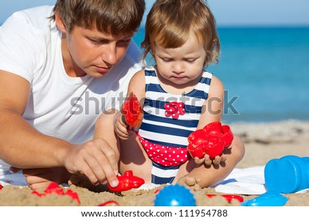 Girl playing with father on the beach