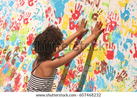 Girl playing with paint. Handprints in different colors in a mural. Casilda Iturrizar Park, Bilbao, Euskadi, Basque Country, Spain.