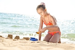 Girl playing with sand on the beach. Girl in a swimsuit molds of sand near the sea