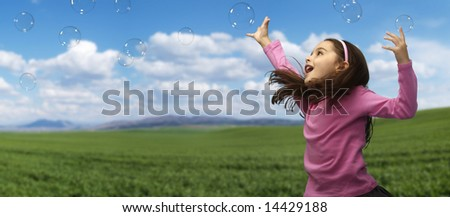 Girl playing with soap bubbles in the field