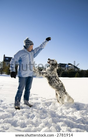 Girl playing with the dog in fresh snow