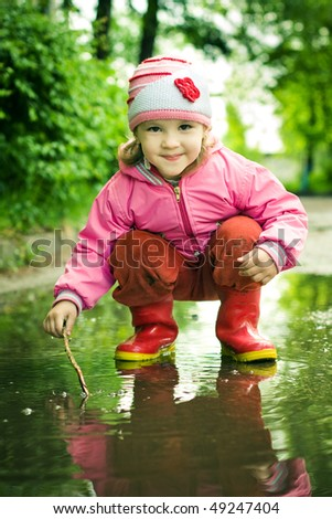 girl plays in the puddle