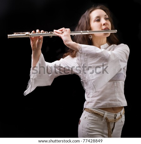 girl plays the flute on a black background