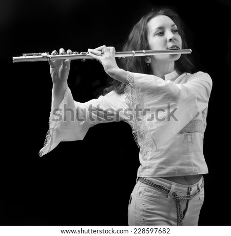 girl plays the flute on a black background.black-and-white photo