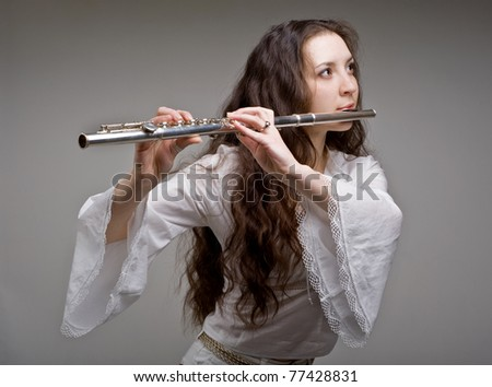 girl plays the flute on a grey background