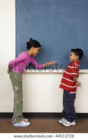 Girl pointing finger at boy in school classroom. Vertically framed shot.