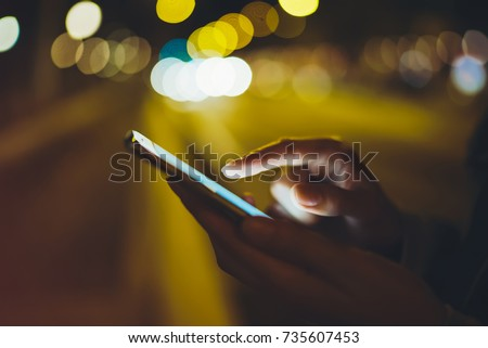 Girl pointing finger on screen smart phone on background illumination glow bokeh light in night atmospheric city, hipster using in hands mobile phone, mockup lights street, online internet concept