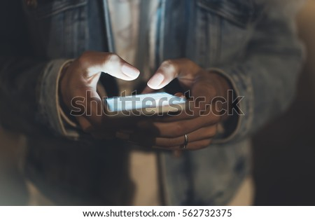 Girl pointing finger on screen smartphone on background illumination bokeh color light in night atmospheric city, hipster using in female hands mobile phone, mockup glitter street, content lifestyle #562732375