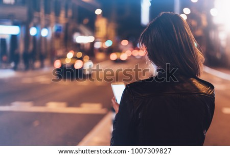 Girl pointing finger on screen smartphone on background illumination glow bokeh light in night atmospheric city, hipster girl using in hands mobile phone, lights auto taxi; mockup glitter street