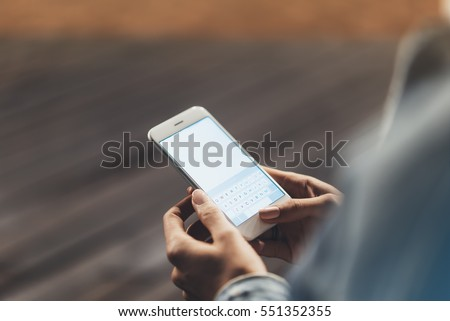 Girl pointing finger on screen smartphone on background wooden floor in night atmospheric city, hipster using in female hands and texting mobile phone, mockup glitter street lifestyle, blured backdrop #551352355