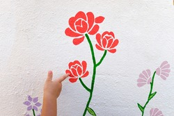 Girl pointing her finger at a drawing of a painted flower on the white wall