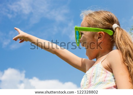 Girl points a finger at an imaginary point in the sky