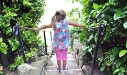 Girl (ponytail)  with colorful clothes standing in a stair outdoor. From the backside. Waiting for something fun during Summer.