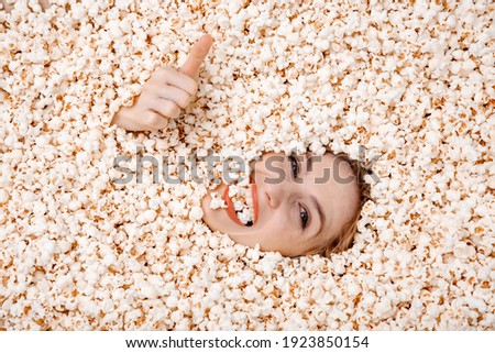Girl portrait in popcorn. Image of beautiful european woman 20s eating popcorn. Pretty female model buried in popcorn with only her face showing. A popcorn background.