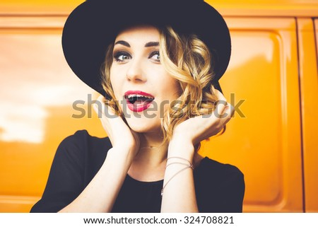 girl portrait of a beautiful young blonde in a black hat with red lips, bright makeup on orange background car smiling and posing lifestyle