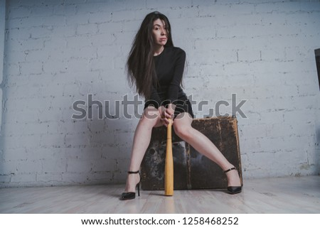 girl posing against a brick wall with a baseball bat in his hands, the concept of a bully or athlete #1258468252