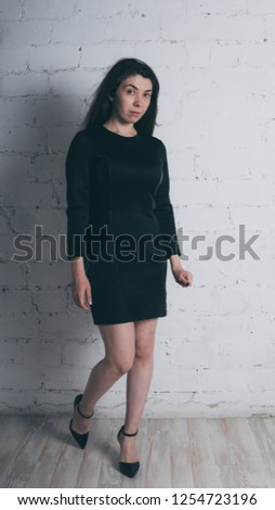 Girl posing against a white brick wall. Model in black dress. Brunette Eastern looks.  #1254723196