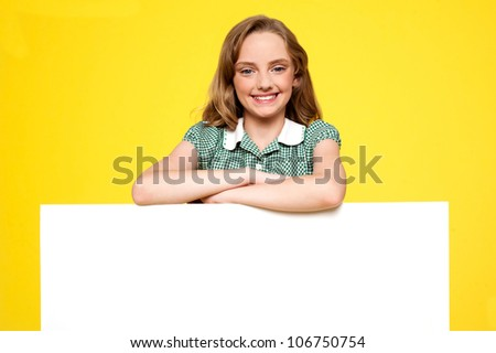 Girl posing behind an advertising board isolated against yellow background