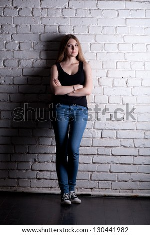Girl posing in studio against a white brick wall #130441982