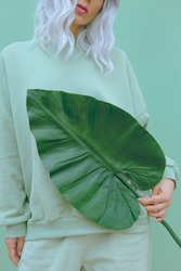 Girl posing in studio. Urban Bio tropical style. Trendy Fresh casual outfit. Fashion mint monochrome aesthetic colours.