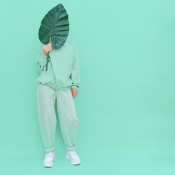 Girl posing in studio. Urban style. Trendy Fresh casual outfit. Fashion mint monochrome aesthetic colours. Bio life tropical mood