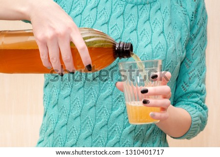 girl pours beer into a glass from a plastic bottle. hands duvush