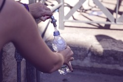 girl pours water into a bottle from street fountain with clean drinking water